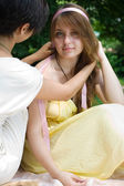 Girl braiding her friends hair outdoors — Stock Photo