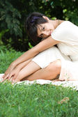 Sensual young brunette sitting on grass — Stock Photo