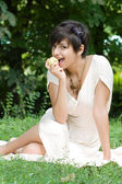 Healthy young girl eating an apple outdoors — Stock Photo