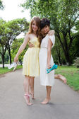 Young girls walking barefoot in the park — Stock Photo