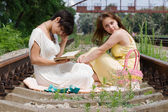 Girls sitting on the railroad carelessly — Stock Photo