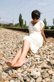 Young girl sitting near the railway — Stock Photo
