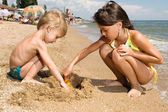 Two young kids digging sand at the beach — Stock Photo