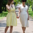 Girls walking in the park joining hands — Stock Photo #3502565