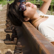 Girl in sunglasses laying carelessly on the railroad — Stock Photo