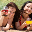 Two young girls drink cocktails at the beach — Stock Photo