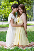 Girls embracing on the coverlet outdoors — Stock Photo