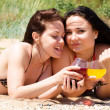 Two young girls drink cocktails at the beach — Stock Photo #3513362