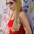 Hip-hop styled girl at graffiti wall — Stock Photo