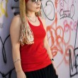 Rapper girl posing at sprayed wall - Stock Photo