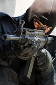 Soldier in black uniform with rifle — Stock Photo