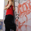 Royalty-Free Stock Photo: Rapper girl posing at graffiti sprayed wall