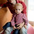 Baby sitting on mother's knees — Stock Photo #3119937