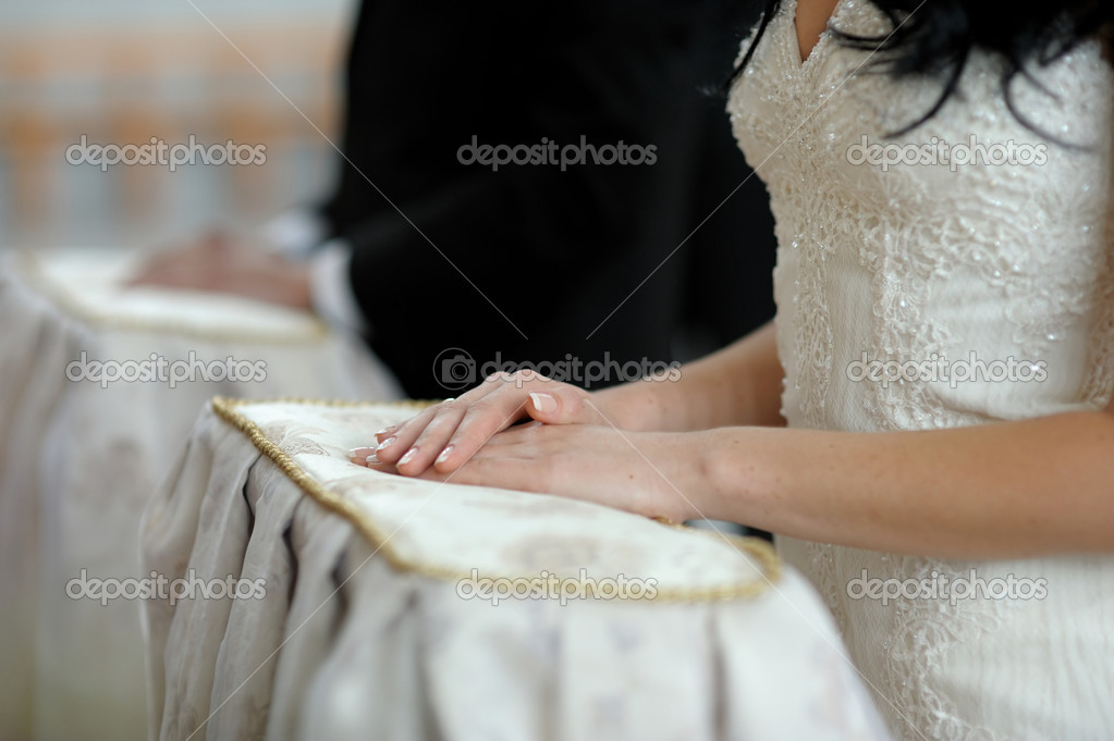 Bride's hands on the pillow close-up during wedding church ceremony — Stock Photo #3119957