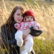 Young mother holding her baby in a meadow - Stock Photo