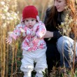 Stock Photo: Young mother with baby in a meadow