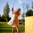 Bride playing golf - Stock Photo