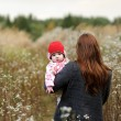 Mother with her baby girl in a meadow - Stock Photo