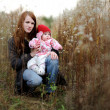 Young mother and her baby in a meadow - Stock Photo