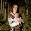 Young mother with her baby in a carrier — ストック写真