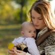 Young mother with her baby in a carrier — Stock Photo #3120107