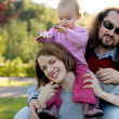 Young family in a park — Stock Photo #3120119