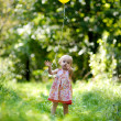 Little baby girl with a yellow balloon — Stock Photo