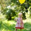 Little baby girl with a yellow balloon — Stock fotografie