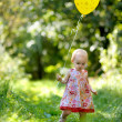 Little baby girl with a yellow balloon - Stock Photo