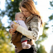 Stock Photo: Young mother with her baby in carrier