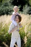 Moeder met een baby op haar schouders wijzend op — Stockfoto