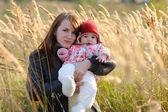 Jeune mère tenant son bébé dans un pré — Photo