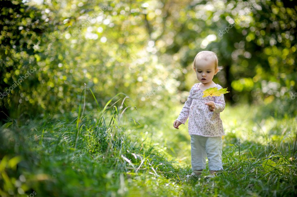 Little baby in a forest holding yellow leaf and looking at it — Stock Photo #3120032