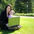 Royalty-Free Stock Photo: Young lady with a baby and a notebook in a park