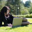 Young lady with a notebook in a park — Stok fotoğraf