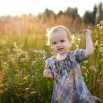Little nice baby walking in a meadow — Stock Photo #3140146