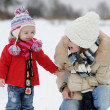 Foto Stock: Little winter baby girl and her young mother