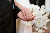 Bride and groom holding each other's hands — Stockfoto
