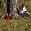 Girls reading  in the park — Stock Photo
