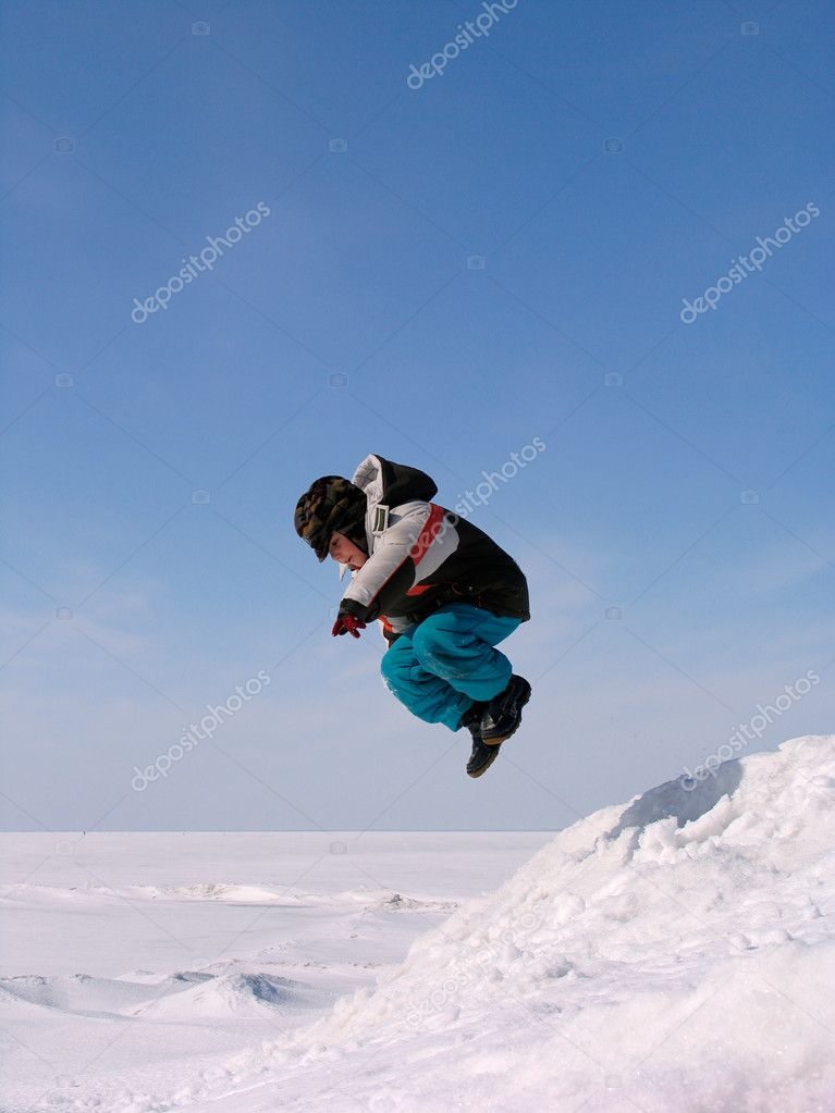 Boy jumping over snow on blue sky — Stock Photo #2721185