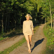 Girl wolking along the forest roud — Stock Photo