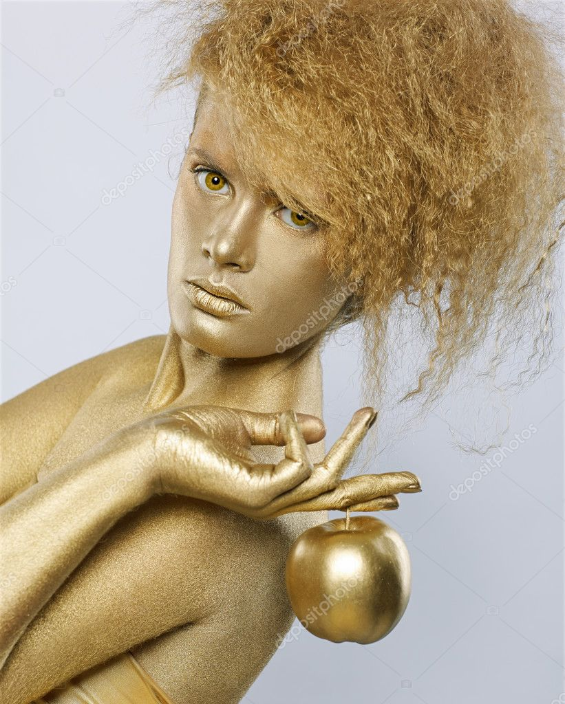 Portrait of girl with golden bodyart posing with golden apple in her hands on gray — Stock Photo #4200094