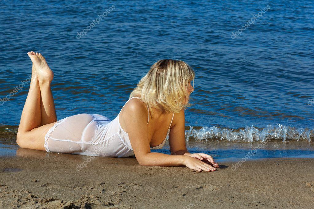 Молодая блонда позирует на берегу моря  116477
