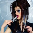 Spider girl licking knife — Stock Photo