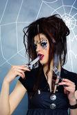 Spider girl licking knife — Stock Photo