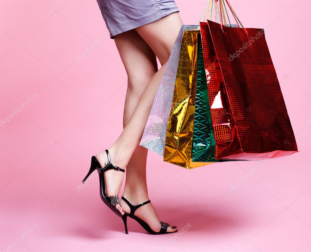 Body part portrait of customer long legged girl in court shoes with shopping bags — Stock Photo #4584031