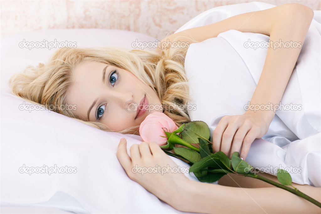 Portrait of beautiful happy blonde girl relaxing in bedroom on linen with pink rose — Stock Photo #4836696
