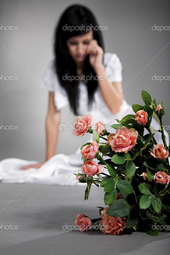 Unhappy bride with rose flower on gray background — Stock Photo #3865187