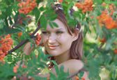 Beautiful girl in the forest with mountain ash — Stock Photo