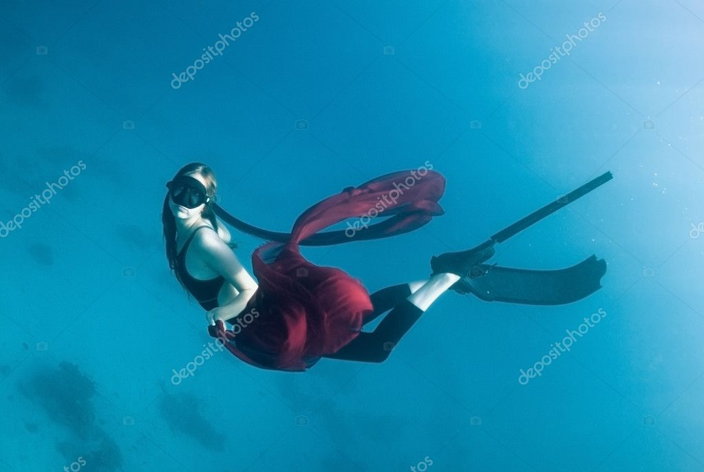 Freediver young girl with a red cloth in the depths of the turquoise sea  Stock Photo #3084088